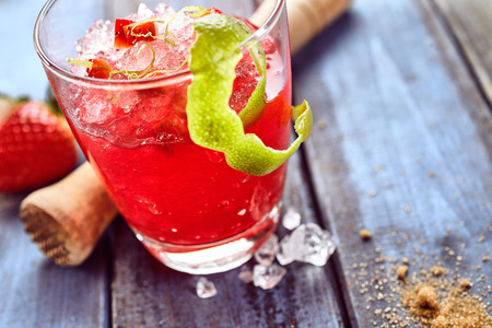 zesty: Red zesty strawberry ice slush drink in glass with lime peel and strawberry next to wooden crusher, spices and ice on table