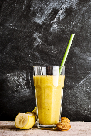energising: Healthy banana and almond smoothie served in a tall glass with fresh ingredients alongside and whole unshelled almond nuts in front of a grungy rustic chalkbaord