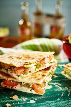 Close up of savory of cooked cheese quesadillas on green cutting board with bottles in background