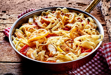 pimientos: Delicious cooked tomato pasta noodles in pan with chopped meat and herbs over red and white napkin with wooden table background