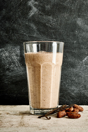 large bean: Large glass of chocolate smoothie on white marble table next to vanilla bean and cacao pods against a black marble background Stock Photo