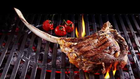 barbecue fire: Single tomahawk rib steak on hot black grill next to three roasted cherry tomatoes with flames underneath