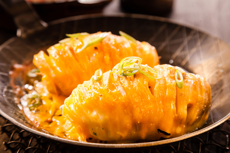 Delicious baked potato sliced through and topped with melted cheese served in a pan for a nutritious appetizer Stock Photo