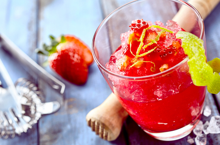 ice tongs: Fresh zesty strawberry ice slush drink with lime peel and strawberry next to crusher and tongs on table Stock Photo