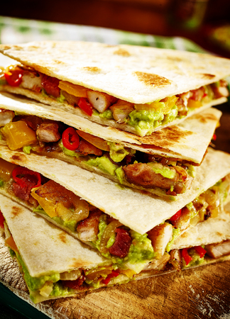 red cooked: Stack of four quesadillas cooked with turkey or pork, guacamole, tomatoes and red peppers Stock Photo