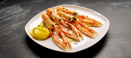 langoustine: High Angle Still Life of Four Cooked Langoustine Shellfish Arranged on Modern White Platter with Lemon Slices and Herbs Resting on Dark Counter Surface