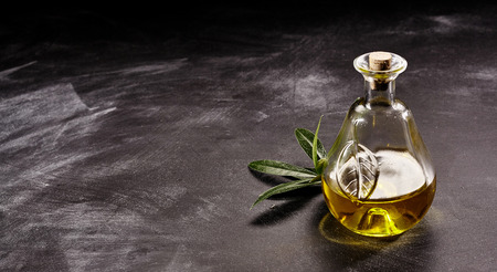 Close Up Still Life of Small Decorative Glass Bottle of Olive Oil with Branch of Olive Leaves on Dark Counter Surface Dusted with Flour, and Ample Copy Space 版權商用圖片