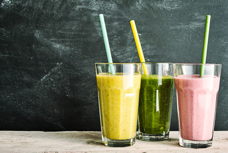 trio: Trio of healthy fruit and vegetable smoothies - berry, kale and banana and almond - with straws on a rustic wooden table with slate background with copy space