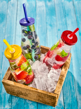refreshment: Top down view on bottles full of ice water and strawberries, blueberries and raspberries in a little box on top of wooden table