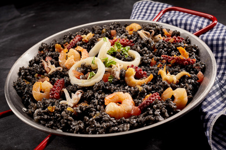 specialty: Single pan full of Catalan specialty called arroz negro with shrimp and onions on napkin over dark stone background