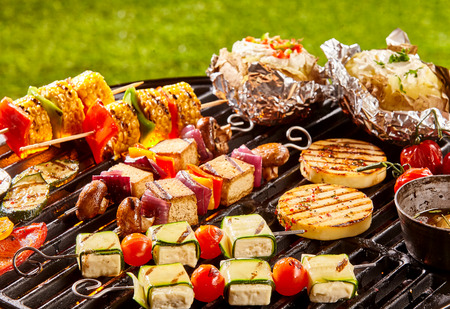 haloumi: Assorted vegetarian meat alternative patties, vegetables, tofu and potatoes next to olive oil on cookout grill