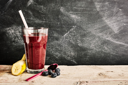 Tall glass of delicious acai berry smoothie in between a slice of banana, blueberries and plastic spoon over background with chalkboard copy space