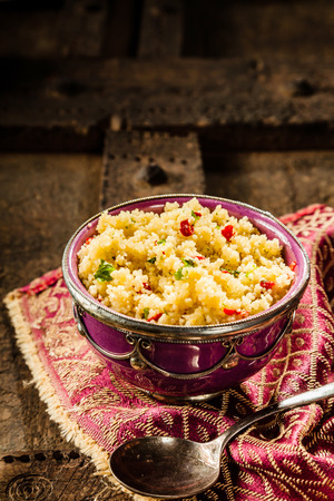 jeweled: High Angle Still Life View of Traditional Morroccan Cuisine, Jeweled Couscous Served with Old Silver Spoon in Ornate Bowl on Decorative Napkin and Rustic Wooden Table with Copy Space