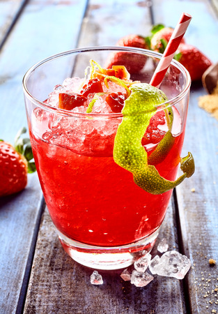 slush: Single serving of red ice slush beverage in glass with red and white straw next to peel of lime hanging on the side and strawberries in background