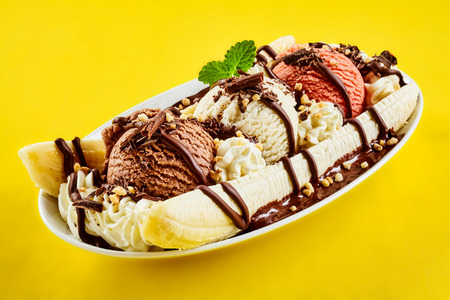 Tropical banana split with chocolate drizzle over three scoops of chocolate, strawberry and vanilla ice cream on fresh bananas, yellow background Stockfoto