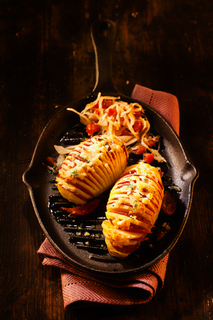 ovenbaked: High Angle Still Life of Sliced Baked Potatoes Garnished with Sliced Salami Meat and Melted Cheese Served on Hot Cast Iron Pan on Rustic Wooden Table