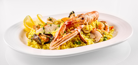 langoustine: Close Up Still Life View of Traditional Spanish Paella Dish Made with Yellow Saffron Rice and Fresh Seafood and Shellfish Served in Modern White Platter on White Background