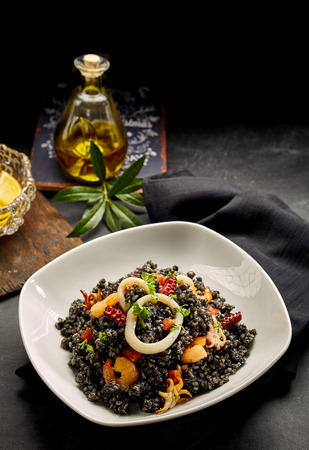 deliciously: Deliciously prepared Catalonian arroz negro recipe garnished with squid and shrimp with bottle of olive oil and black napkin in background