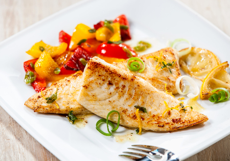 fillets: Close up of fresh tilapia fish fillet wit bbq grilled vegetables on white dish or plate on wooden background