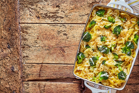 top down: Top down view on delicious broccoli casserole in rectangular pan with copy space over weathered wooden table Stock Photo