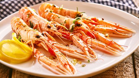 langoustine: High Angle Still Life of Four Cooked Langoustine Shellfish Arranged on Modern White Platter with Lemon Slices and Herbs Resting on Rustic Wooden Table with Checkered Cloth Napkin Stock Photo
