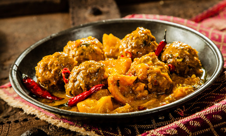 smothered: Close Up Still Life of Traditional Tajine Berber Dish of Meatballs Smothered in Spicy Yellow Curry Sauce with Hot Red Peppers and Served in Shallow Bowl on Cloth Napkin and Rustic Wooden Table Stock Photo