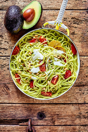 spaghetti: Tropical avocado, tomato and parmesan Italian noodles or pasta garnished with lemon on an old rustic wooden table with a fresh ripe halved avocado pear to the side, overhead view