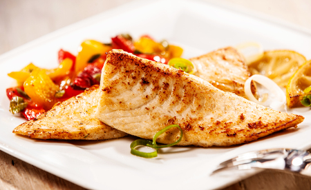fillets: Two marinated grilled fresh tilapia fillets served with colorful roasted vegetables as a delicious seafood appetizer to dinner