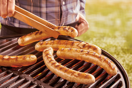 unidentifiable: Unidentifiable person using wooden tongs to turn over various hot dog sausages on hot grill outdoors Stock Photo