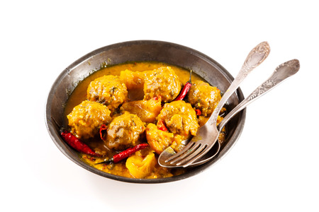 smothered: High Angle View of Traditional Tajine Berber Dish of Meatballs Smothered in Spicy Yellow Curry Sauce with Hot Red Peppers and Served in Shallow Bowl with Cutlery on White Background