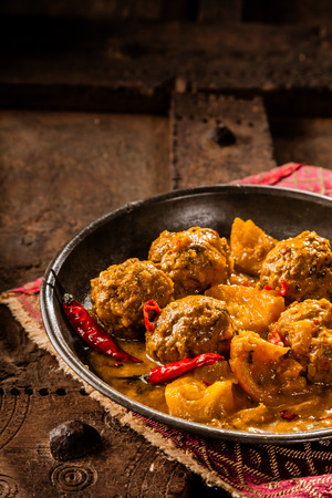 Close Up Still Life of Traditional Tajine Berber Dish of Meatballs Smothered in Spicy Yellow Curry Sauce with Hot Red Peppers and Served in Shallow Bowl on Cloth Napkin and Rustic Wooden Table Stock Photo
