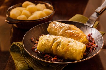 repollo: Sabrosos rollos de repollo blanco con un relleno de carne molida picante servido en una vieja sartén con un plato de patatas en un restaurante rústico o en la cocina