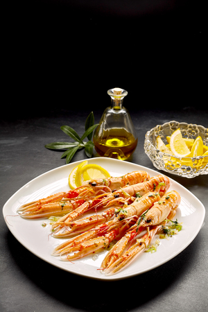 shellfish: Four Cooked Langoustine Shellfish Served on White Platter with Lemon Wedges and Small Bottle of Olive Oil on Dark Counter Table Surface with Copy Space