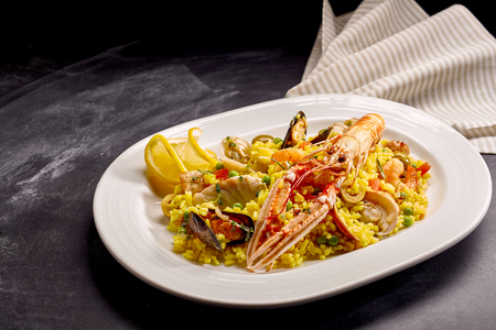 langoustine: High Angle Still Life View of Traditional Spanish Paella Dish Made with Yellow Saffron Rice and Fresh Seafood and Shellfish Served on Modern White Platter on Dark Counter with Copy Space and Napkin
