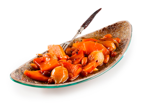 sauce dish: Still Life of Traditional Tajine Vegetable Dish Made with Bright Orange Vegetables in Sauce and Served in Long Narrow Modern Dish with Fork on White Background with Copy Space
