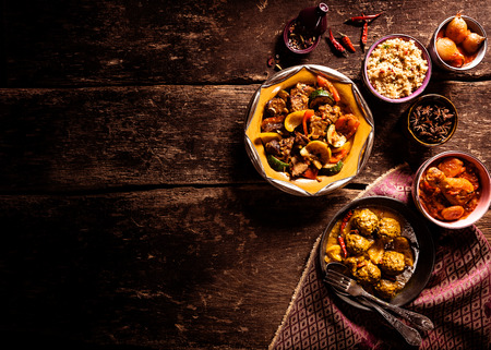 High Angle View of Traditional Tajine Dishes and Fresh Ingredients Served on Rustic Wooden Table with Cloth Napkin and Ample Copy Space