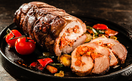 Gourmet Food Close Up of Roast Pork Roll Stuffed with Tomatoes and Grilled Vegetables and Served on Sizzling Cast Iron Pan and Rustic Wooden Table