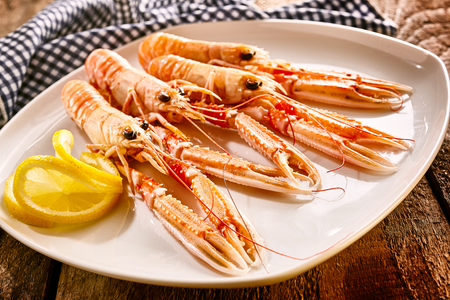garnish: Close Up Still Life of Four Cooked Langoustine Shellfish Arranged on Modern White Platter with Lemon Slices and Resting on Rustic Wooden Table with Checkered Cloth Napkin