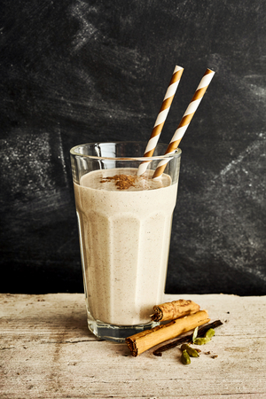 Silky dairy drink in tall glass with two swirl colored straws on a long rustic table with a sprinkle of cinnamon