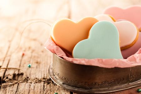 feestelijk: Feestelijke hartvormige fondant koekjes met kleurrijke beglazing op een rustieke houten tafel met een kopie ruimte voor Valentijnsdag, verjaardag of bruiloft te vieren