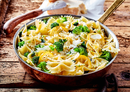 freshly cooked: Metal frying pan full of freshly cooked savory broccoli bow tie pasta and lemon slices on worn out wooden table