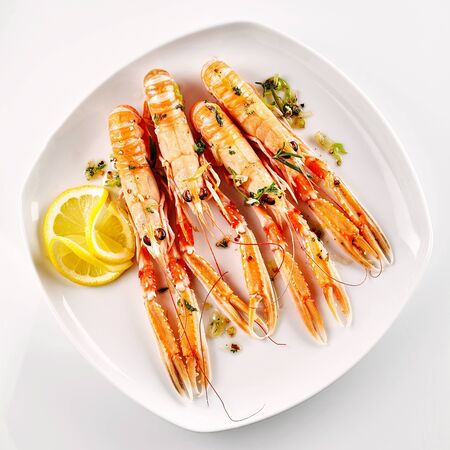 garnish: High Angle Still Life View of Four Cooked Langoustine Shellfish Served on Modern Square White Plate with Lemon Slices and Herb Garnish on White Background