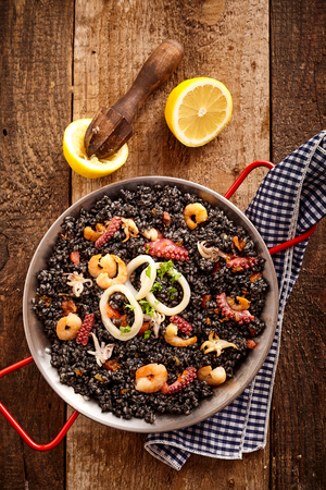 steel pan: Top down view of delicious steel pan of arroz negro, fried shrimp and onion rings in holder on top of wooden table with lemon halves