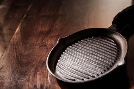 cast iron: Empty clean cast iron griddle pan on a rustic wooden table with copy space, high angle view