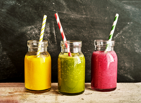 Three tasty fresh healthy smoothies served in glass jars with tropical mango and raspberry and fresh green kale on a rustic wooden table Foto de archivo