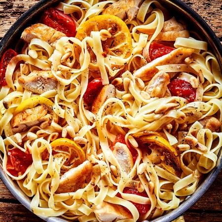 pasta: Fettucine o tallarines de pasta italianas de la cinta con el pollo, el tomate, la ralladura de limón y el chile en una deliciosa receta casera, vista aérea de cerca