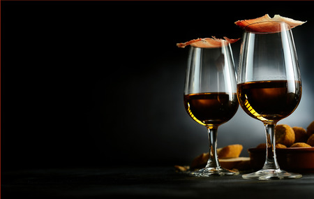 bacalao: Spanish tapas and sherry aperitif with slices of gourmet ham balancing on top of the glasses with a bowl of bacalao croquettes over a dark background with copy space
