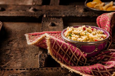 Nature morte de plat traditionnel marocain Jeweled Couscous Side Servi dans Ornement Bowl Haut de la décoration et de serviette de table en bois rustique avec Espace texte Banque d'images - 54713795