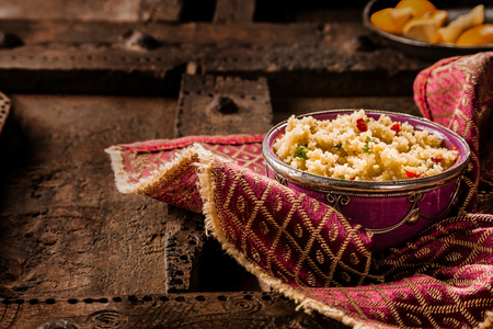 Still Life of Traditional Morroccan Jeweled Couscous Side Dish Served in Ornate Bowl on Top of Decorative Napkin and Rustic Wooden Table with Copy Space Stock Photo