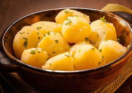 papas: Plato de patatas pequeñas hervidas adornado con perejil fresco picado para un acompañamiento a una comida sabrosa